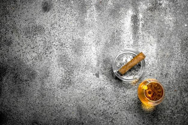 Glas cognac mit einer zigarre.