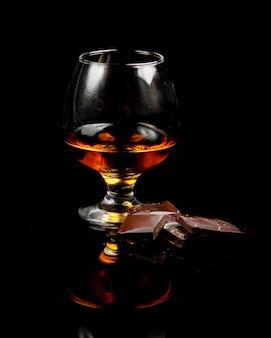 Glas cognac und dunkle schokolade