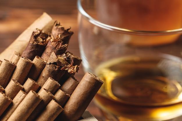Glas cognac und gerollte zigarren auf holztisch