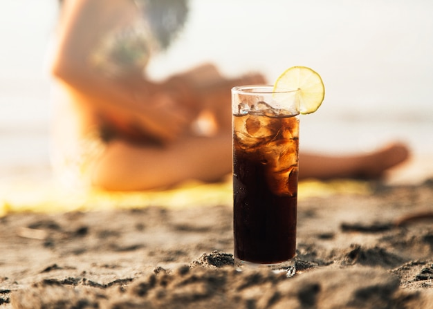 Glas cola mit eis am strand