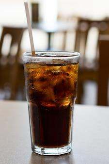 Glas cola mit eis auf einer tabelle