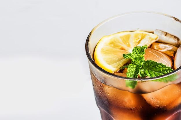 Glas cola mit zitrone und aromatischen blättern