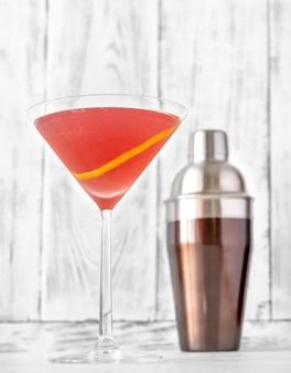 Glas cosmopolitan cocktail mit zitronenschale garniert