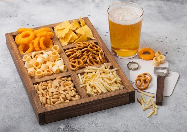 Glas craft-lagerbier und öffner mit schachtel mit snacks auf leichtem küchentisch. brezel, salzige kartoffelstangen, erdnüsse, zwiebelringe mit nachos in vintage-box mit öffnern und bierdeckeln.