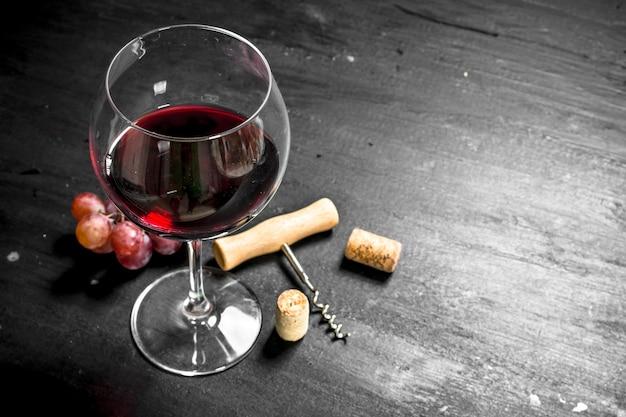 Glas cran wine mit einem korkenzieher und einem zweig trauben an der schwarzen tafel