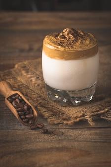 Glas dalgona-kaffee auf rustikalem tisch