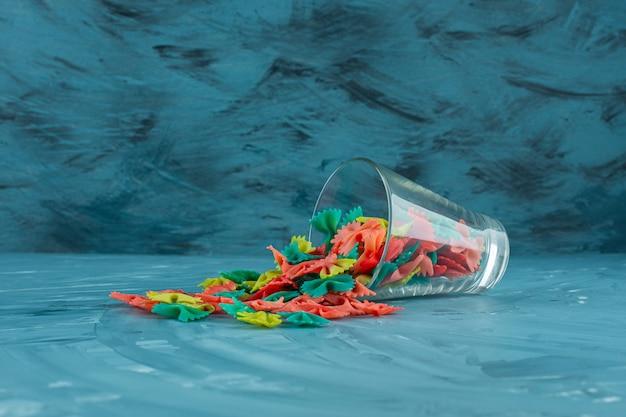 Glas der bunten rohen farfalle nudeln auf blauem hintergrund.