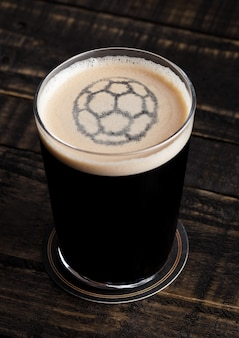 Glas der starken bierspitze mit fußballformform auf hölzernem hintergrund