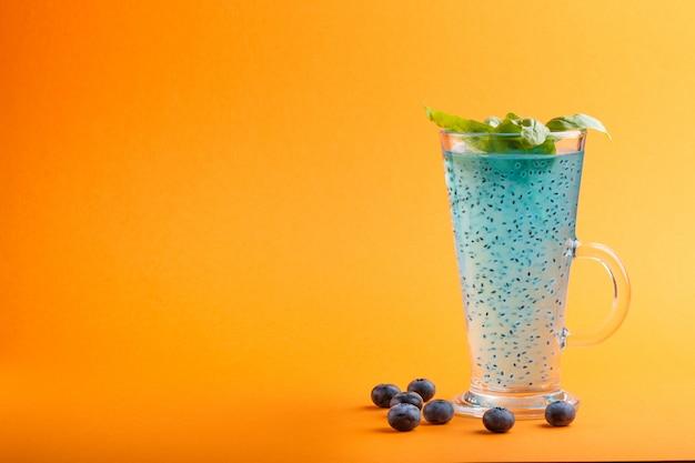 Glas des blaubeerblaus färbte getränk mit basilikumsamen auf orange. morninig, frühling, gesundes getränkkonzept. seitenansicht