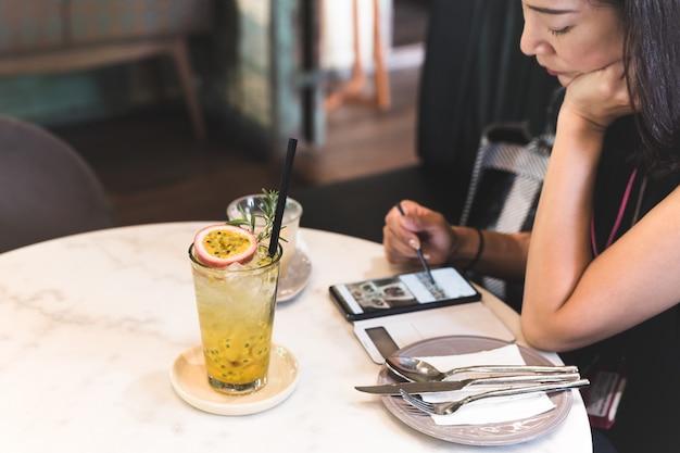 Glas des frischen passionsfruchtgetränks auf tisch mit frau, die handy verwendet.