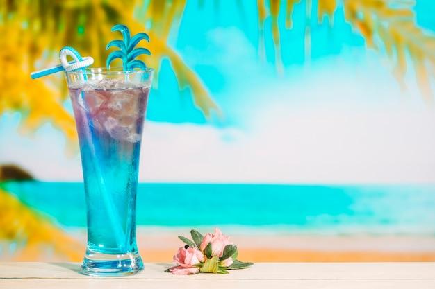Glas des geschmackvollen blauen getränks und der rosa blume