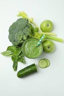 Glas des grünen smoothie und der bestandteile auf weißem hintergrund, draufsicht