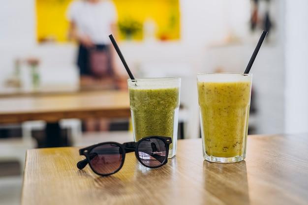 Glas des leckeren gesunden smoothie auf tisch im sommercafé.