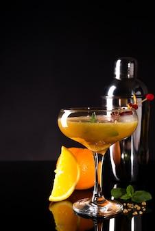 Glas des orange alkoholischen getränks mit eis und scheibe der orange schale auf dem dunklen hintergrund