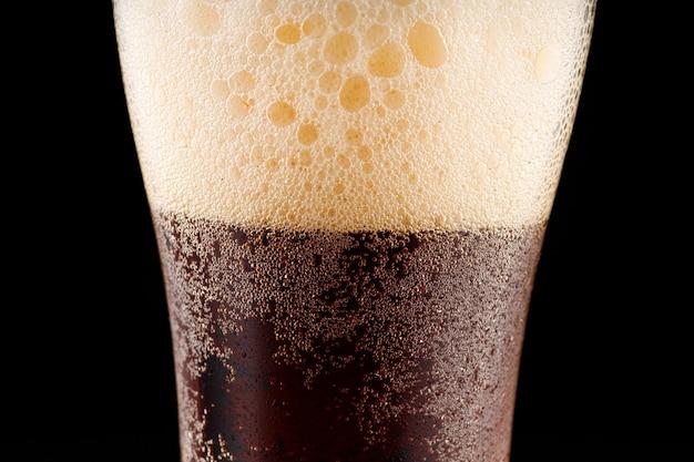 Glas dunkles bier und blasen