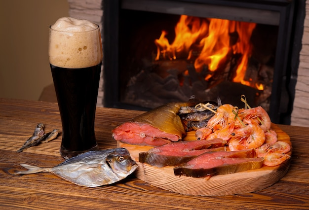 Glas dunkles bier und ein tablett mit verschiedenem fisch auf dem hintergrund eines brennenden kamins