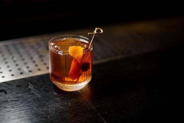Glas eines altmodischen cocktails auf der bartheke aus holz?