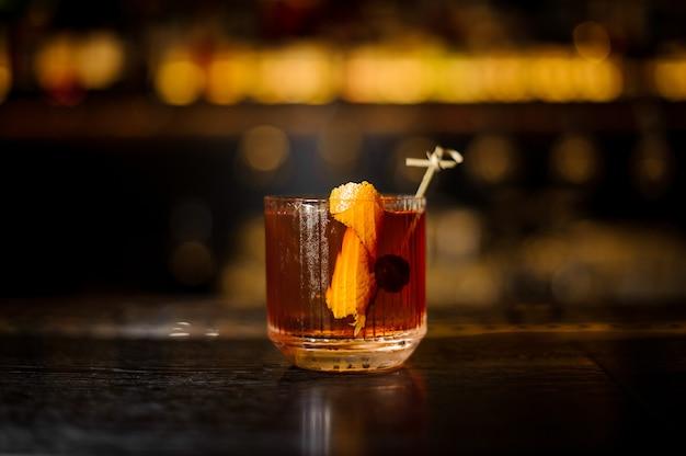 Glas eines altmodischen cocktails auf der hölzernen bartheke
