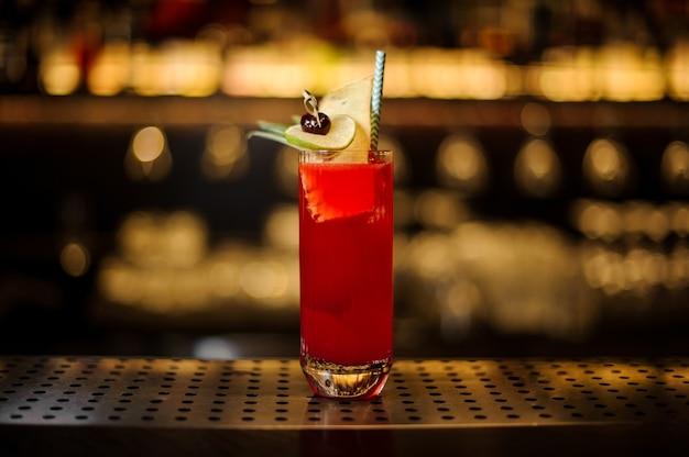 Glas eines hurricane punch-cocktails, dekoriert mit limette und getrockneter ananas auf der bartheke aus holz