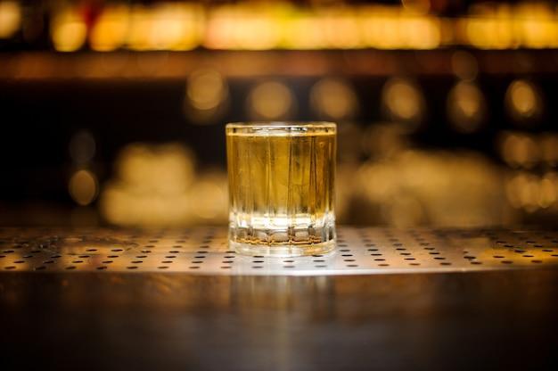Glas eines rusty nail cocktails auf der hölzernen bartheke aus stahl