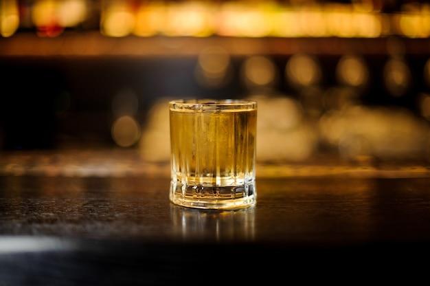 Glas eines rusty nail cocktails auf der hölzernen bartheke