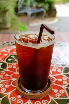 Glas eiskaffee auf der bunten tabelle an der garten-terrasse