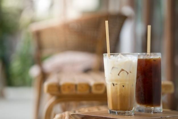 Glas-eiskaffee mit milch auf holztisch im freien anprobieren