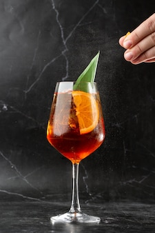 Glas eiskalter aperol spritz cocktail serviert in einem mit orangenscheiben dekorierten weinglas