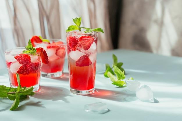 Glas erdbeer-soda-getränk auf hellblau. sommer gesunde entgiftungslimonade, cocktail oder ein anderes getränk