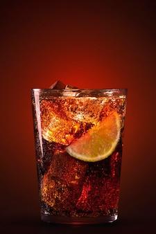 Glas erfrischendes cola-getränk mit eis und zitrone auf dunklem hintergrund