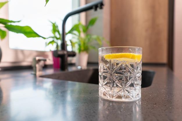 Glas erfrischendes wasser mit einer spritzigen zitronenscheibe in einem niedrigen winkel auf einer arbeitsplatte in einer küche mit kopienraum