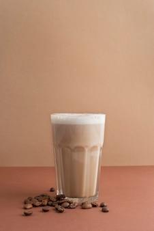 Glas frappekaffee mit kaffeebohnen daneben