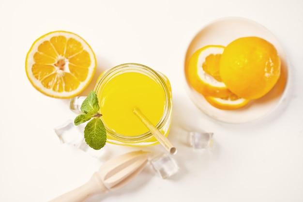 Glas frische limonade mit minze. geschnittene zitrone auf hintergrund. draufsicht.
