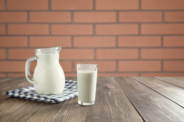 Glas frische milch und krug auf hölzerner tischplatte mit unschärfeküche als hintergrund für montageprodukt.