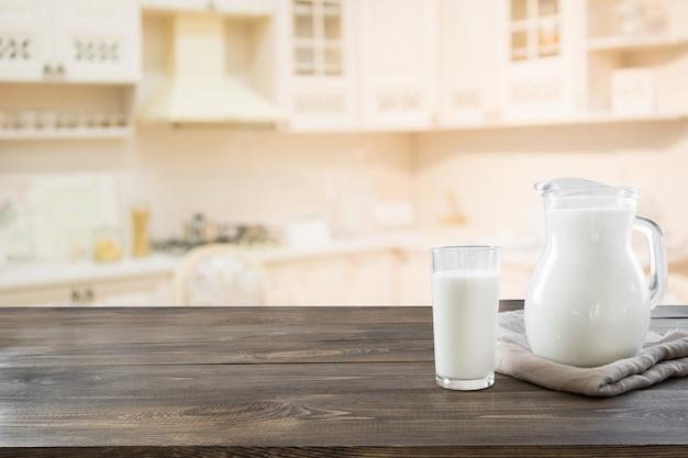 Glas frische milch und krug auf hölzerner tischplatte mit unschärfeküche als hintergrund.