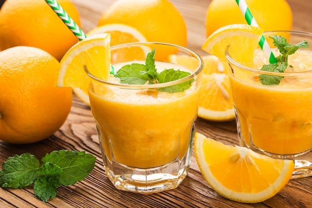 Glas frischen orangensaft mit frischen früchten auf holztisch