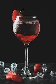 Glas frischer erdbeercocktail auf schwarzem rauchtisch