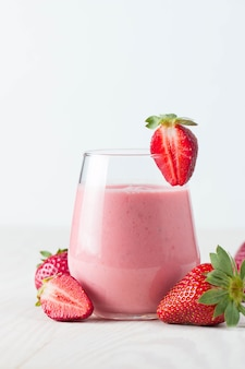 Glas frischer erdbeermilchshake, smoothie und frische erdbeeren auf rosa, weißem und hölzernem hintergrund. gesundes essen und trinken konzept.