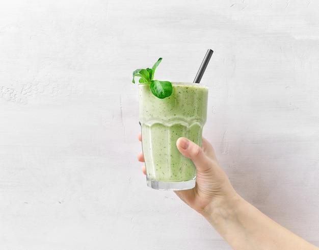Glas frischer grüner smoothie in menschlicher hand