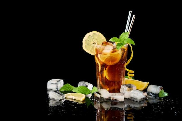 Glas frischer long island eistee cocktail studio auf schwarzem hintergrund geschossen