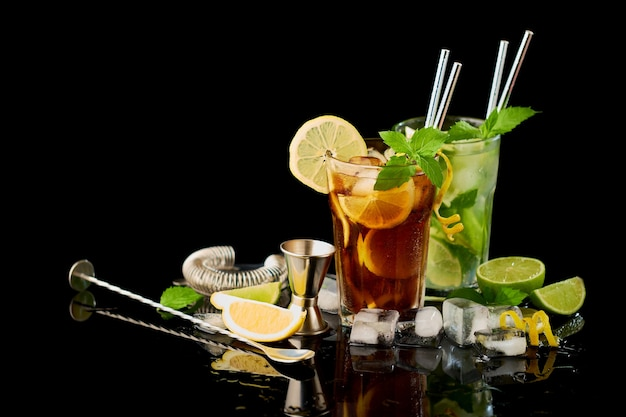 Glas frischer long island eistee und mojito cocktail studio auf schwarzem hintergrund gedreht