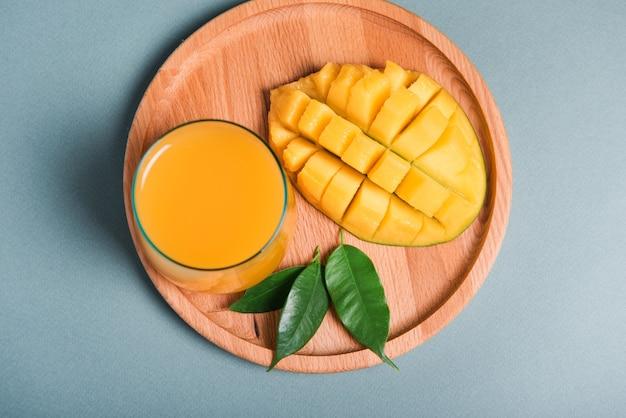 Glas frischer mangosaft und orangenscheibe auf grauem hintergrund. selektiver fokus