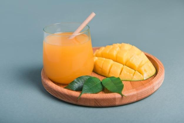 Glas frischer mangosaft und scheibe mangofrucht auf grauer oberfläche. selektiver fokus
