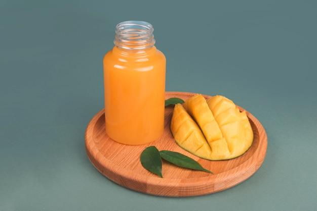 Glas frischer orangen- und mangosaft und mangoscheibe