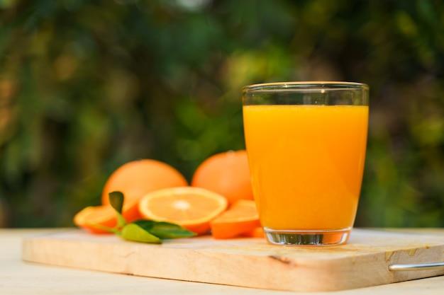 Glas frischer orangensaft mit frischen früchten auf holz