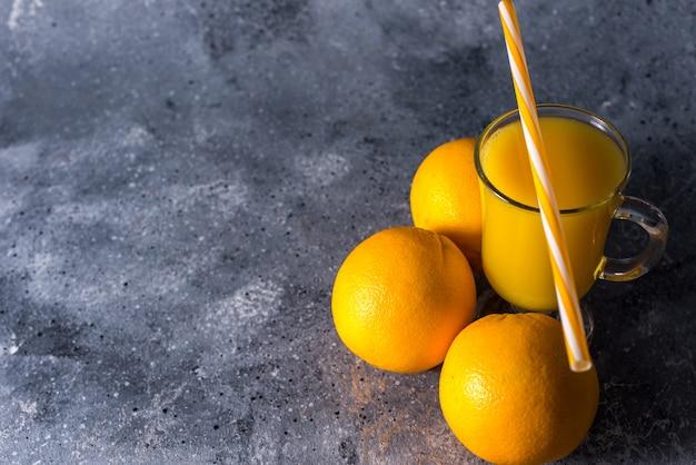 Glas frischer orangensaft, reife orangenfrüchte und scheiben