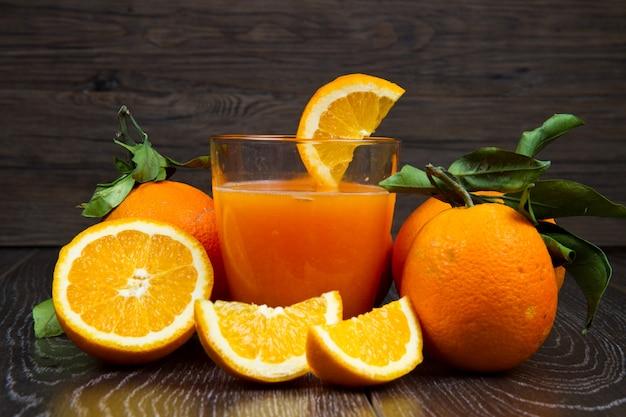 Glas frischer orangensaft und orangen auf hölzernem hintergrund