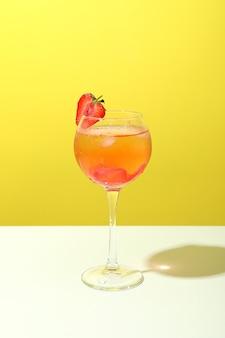 Glas frischer sommercocktail vor gelbem hintergrund
