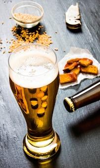 Glas frisches bier auf einem schwarzen hölzernen hintergrund.