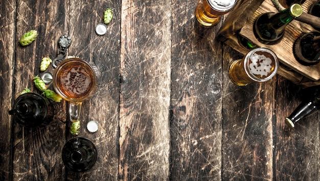 Glas frisches bier mit flaschen und korken auf holztisch.